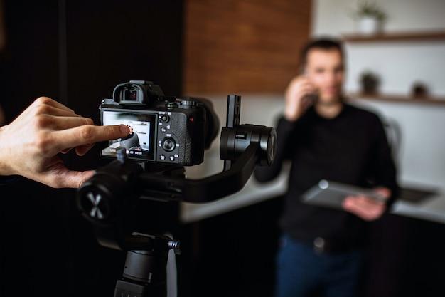 Il dito del cameraman punta sullo schermo della telecamera. registrare video o scattare foto di un giovane imprenditore in cucina parlando al telefono. tenere il laptop e lavorare in remoto. ha affari propri. muro sfocato.