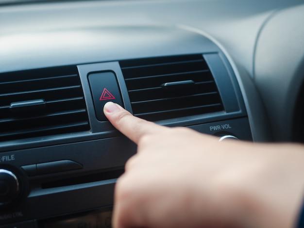 Il dito del conducente che preme il pulsante di emergenza dell'automobile in macchina