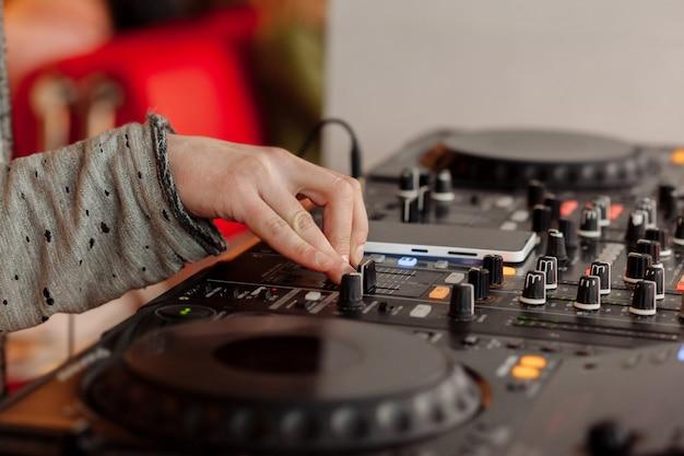 Il dj che gioca musica al primo piano del miscelatore. messa a fuoco selettiva