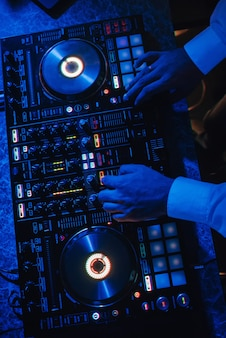 Il dj suona con un mixer musicale in una discoteca