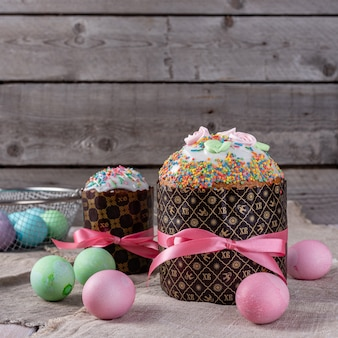 Il dolce di pasqua, ha dipinto le uova con i tulipani su un vecchio fondo rustico di legno.