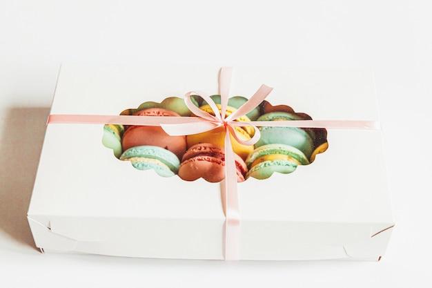 Il dolce macaron o il maccherone di verde giallo rosa blu variopinto della mandorla dolce agglutina in contenitore di regalo isolato su bianco. biscotto dolce francese concetto minimo di panetteria alimentare. vista piana laica, copia spazio