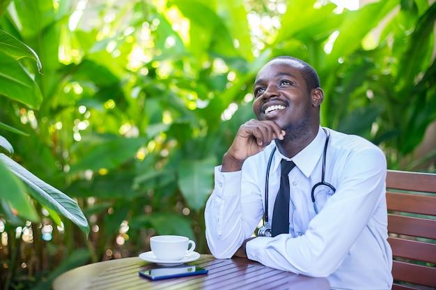 Il dottore africano sta progettando il suo futuro. è seduto e sorridente con lo sfondo verde della natura.