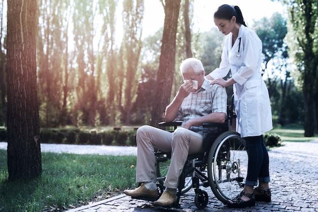 Il dottore conforta il vecchio piangente nel parco estivo