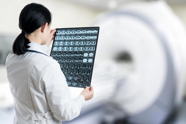 Il dottore controlla la radiografia del cervello dal cervello di scansione del ct all'ospedale della stanza paziente.
