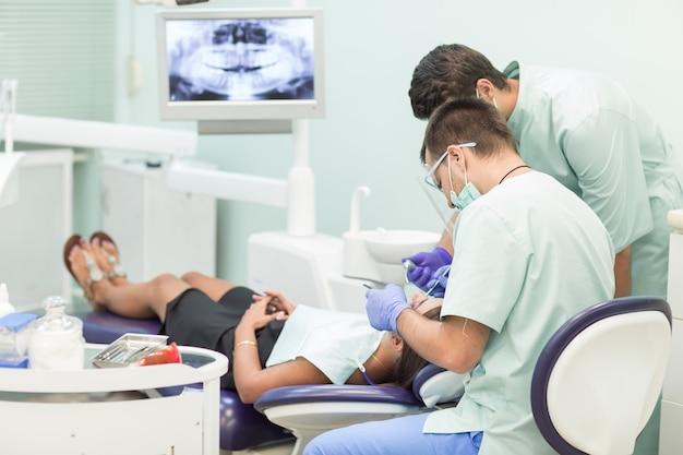 Il dottore dentista con un assistente lavora in una clinica dentale.