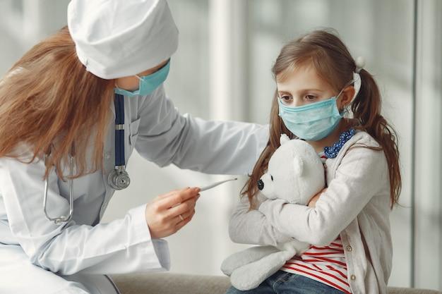Il dottore e un bambino in maschera protettiva sono in ospedale