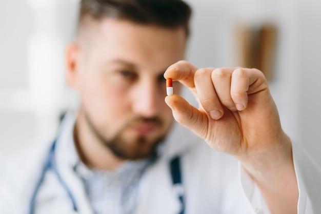 Il dottore in white coat on shoulder nel gabinetto scrive la ricetta per il paziente. concetto di ospedale medico sanitario