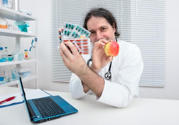Il dottore offre una mela come alternativa salutare alle pillole