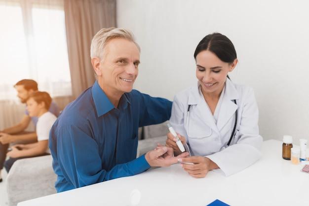 Il dottore prende il sangue dal dito dell'uomo anziano.