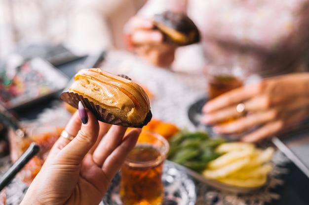 Il eclair del caramello della tenuta della donna è servito per la messa a punto del tè