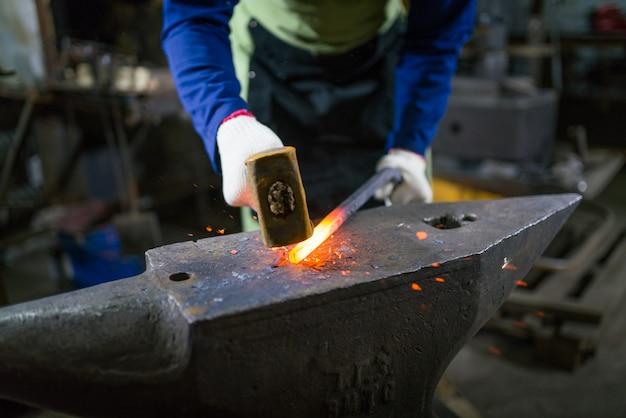 Il fabbro forgia il metallo luminoso nella fornace, calcia le scintille