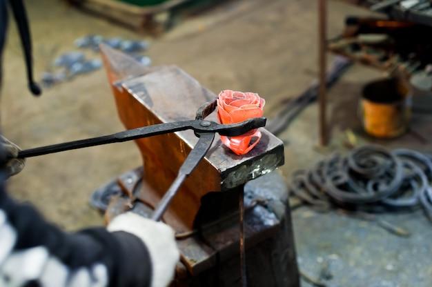 Il fabbro forgia l'acciaio rosa sull'incudine