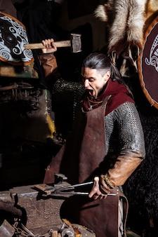 Il fabbro vichingo forgia armi nella vecchia fucina d'epoca.