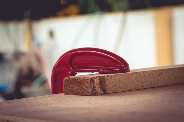 Il falegname fissa i morsetti su una superficie di legno per un migliore incollaggio.
