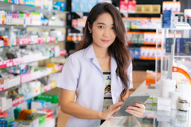 Il farmacista femminile asiatico utilizza la compressa digitale nella farmacia