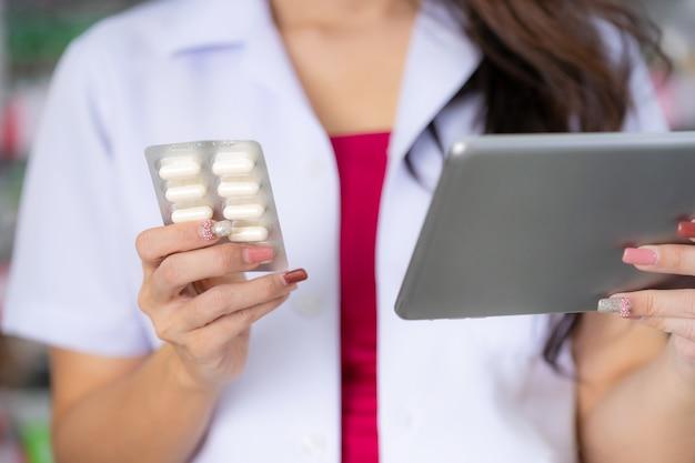 Il farmacista tiene una scatola di medicinali in farmacia