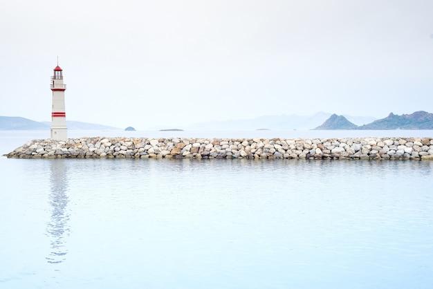 Il faro in un mare nebbioso mostra la direzione - concetto di solitudine e speranza