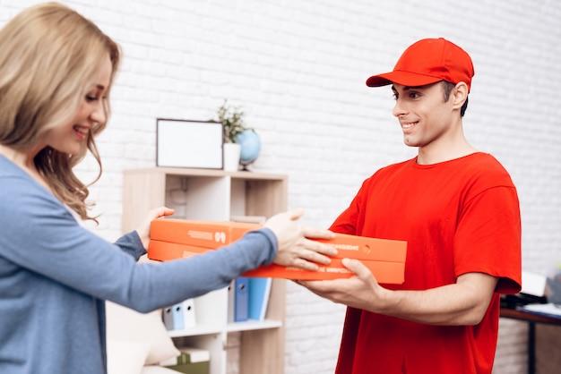 Il fattorino arabo dà alla ragazza sorridente la scatola della pizza.