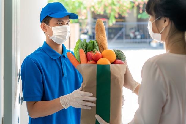 Il fattorino asiatico che indossa la maschera e il guanto con la borsa della spesa di cibo, frutta, verdura danno alla donna cliente davanti alla casa durante il periodo di isolamento domestico.