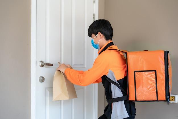 Il fattorino asiatico invia un sacchetto di cibo alla maniglia della porta per contatto senza contatto o senza contatto dal cavaliere di consegna nella casa di fronte per il social distanza per il rischio di infezione. concetto di coronavirus