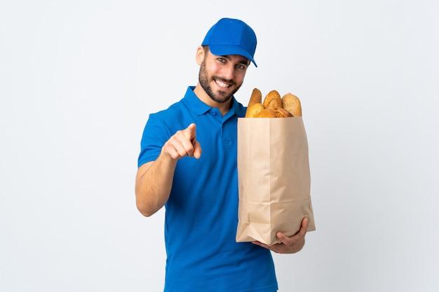 Il fattorino che giudica una borsa piena di pani isolati sulla parete bianca indica il dito voi con un'espressione sicura