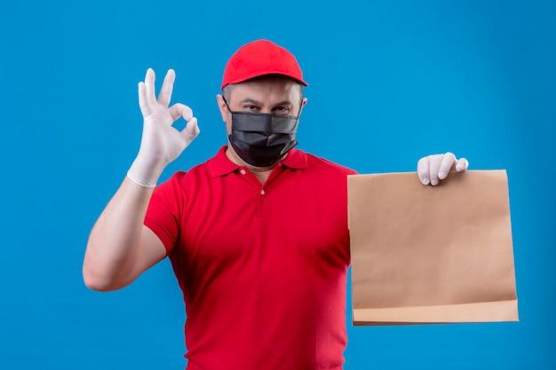 Il fattorino che indossa l'uniforme rossa e il cappuccio in maschera protettiva facciale che tiene il pacchetto di carta positivo e felice facendo bene firma sopra la parete blu