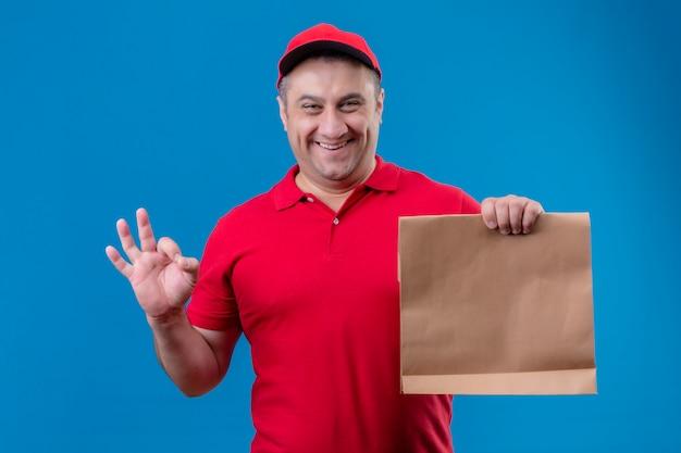 Il fattorino che indossa l'uniforme rossa e la protezione che tengono il pacchetto di carta che sembra positivo e felice facendo bene firmano sopra la parete isolata blu