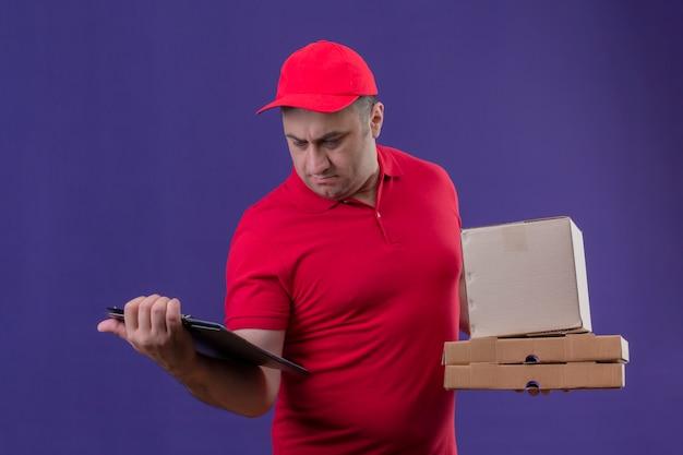 Il fattorino che indossa l'uniforme rossa e la protezione che tengono le scatole di cartone che esaminano con il fronte serio la lavagna per appunti in altra consegnano la parete porpora isolata