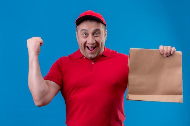 Il fattorino che porta l'uniforme rossa e ricopre il pacchetto di carta della tenuta uscito e pugno d'innalzamento felice dopo una vittoria sopra la parete blu isolata