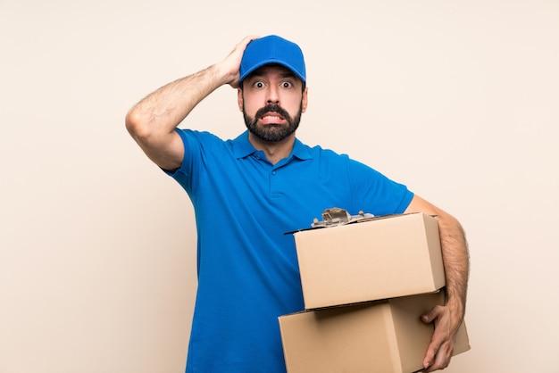 Il fattorino con la barba sopra la parete isolata frustrato e prende le mani sulla testa
