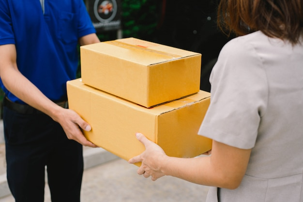 Il fattorino dà le scatole di cartone alla giovane donna