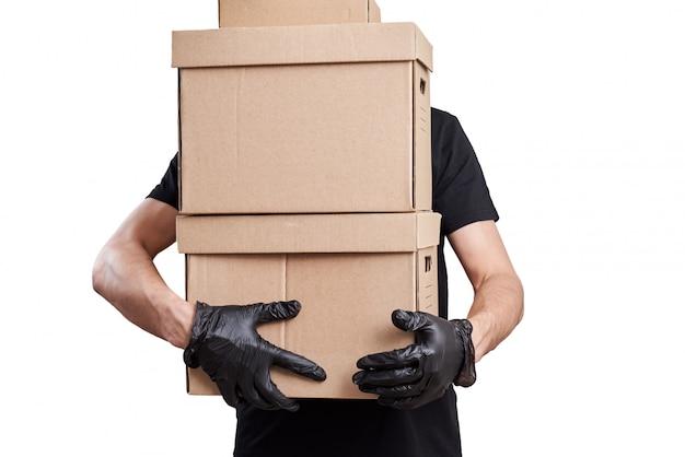 Il fattorino in uniforme nera con guanti tiene la scatola di cartone
