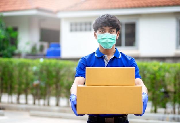 Il fattorino indossa guanti e maschere per contenere scatole di cartone