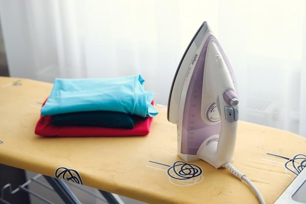 Il ferro è sulla tavola da stiro, accanto ai vestiti.