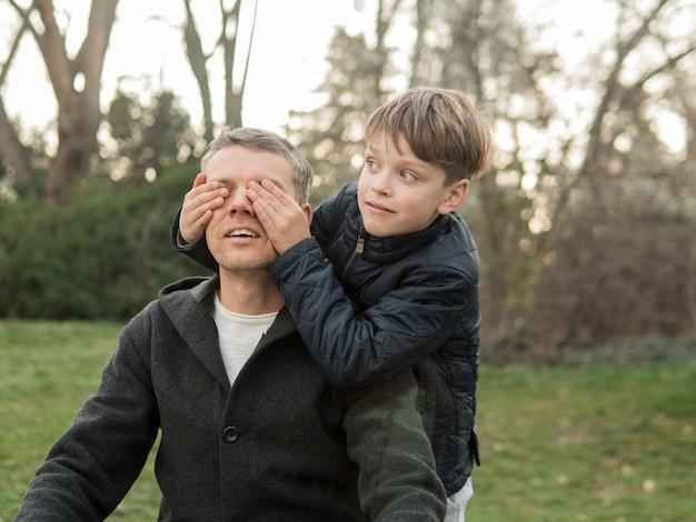 Il figlio copre gli occhi di suo padre nel parco