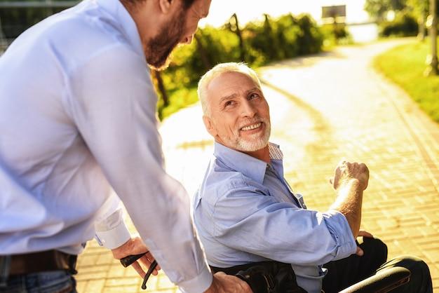 Il figlio trasporta l'uomo disabile sulla sedia a rotelle.
