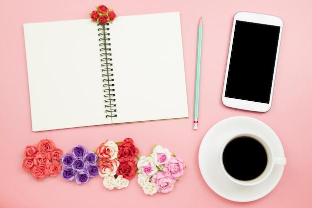 Il fiore del caffè del nero del telefono cellulare del taccuino è aumentato su fondo rosa