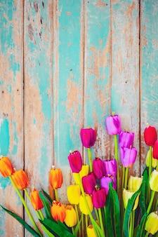 Il fiore del tulipano fiorisce su fondo di legno d'annata, progettazione della struttura del confine. tono di colore vintage - concetto di fiore di primavera o estate sfondo