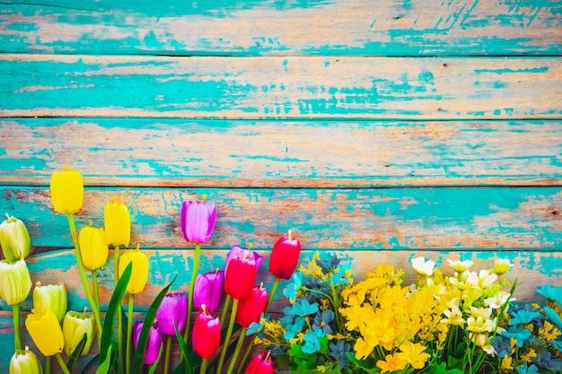 Il fiore del tulipano fiorisce su fondo di legno d'annata, progettazione della struttura del confine