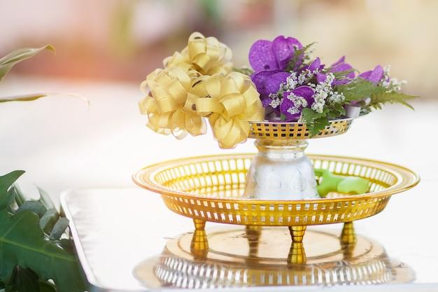 Il fiore viola e il nastro d'oro nel vassoio con piedistallo. concetti di celebrazione.