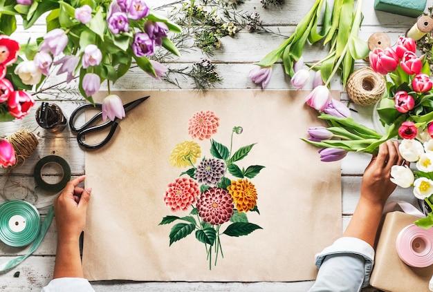 Il fiorista che mostra la carta dello spazio di progettazione vuota sulla tabella di legno con i fiori freschi decora