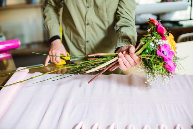 Il fiorista maschio passa la fabbricazione del mazzo dei fiori