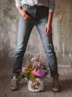 Il fiorista professionista della camicia di jeans alla moda della donna tiene il vaso di fiori selvaggi della composizione negozio di fiori, muro di cemento, grigio.