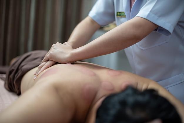 Il fisioterapista sta controllando le anomalie del corpo dopo il trattamento a coppa.