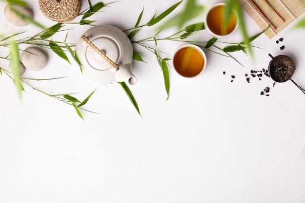 Il fondo asiatico dell'alimento ha messo con tè verde, le tazze e la teiera con i rami di bambù
