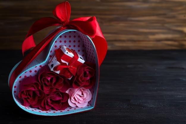 Il fondo dei biglietti di s. valentino con i cuori rossi e è aumentato in contenitore di regalo su fondo di legno scuro