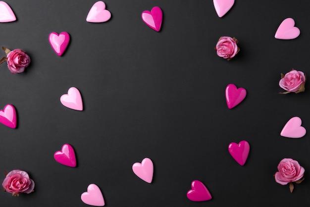 Il fondo del giorno di biglietti di s. valentino con i cuori rossi e è aumentato sul fondo nero dello spazio della copia.