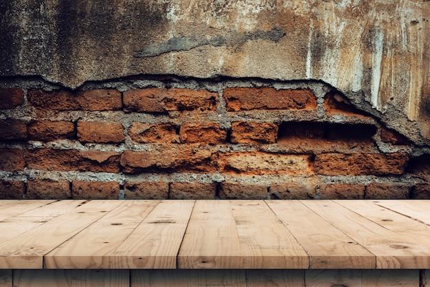 Il fondo del muro di mattoni e la tavola di legno vuota visualizzano il montaggio per il prodotto con lo spazio della copia.