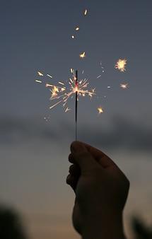 Il fondo della mano della gente sta giocando con gli sparklers del fuoco sull'oscurità al festival.
